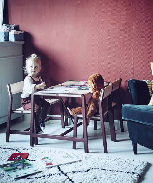 Малко момиченце седящо на детска маса в червена стая.