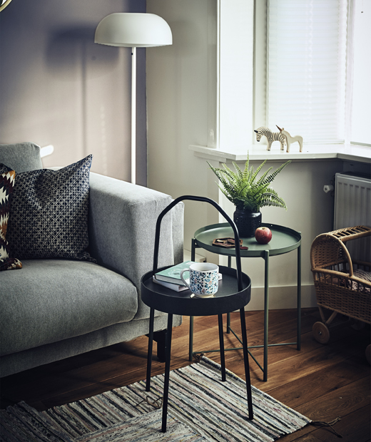 Две малки, кръгли масички до диван в дневната.