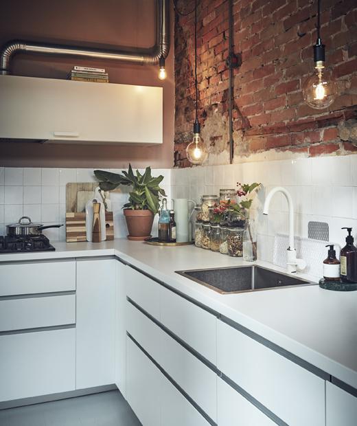 Бяла кухня с открита тухлена стена.