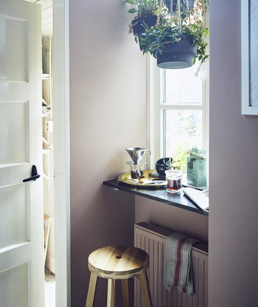 Стол пред прозорец с висящи растения и прибори за приготвяне на кафе