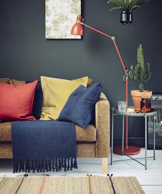 Боядисана в тъмно стая с диван, осветление и текстили.