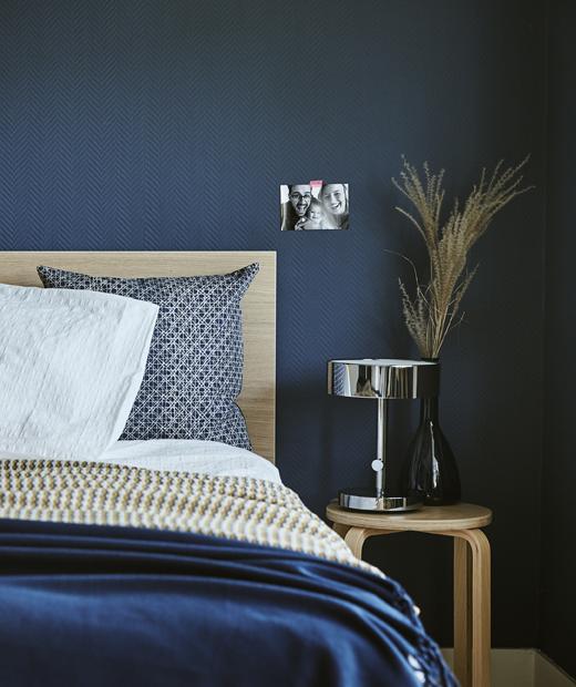 Тъмносиня спалня с легло и столче.