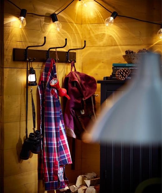 Стена със закачалки с окачени дрехи, над която светят лампи