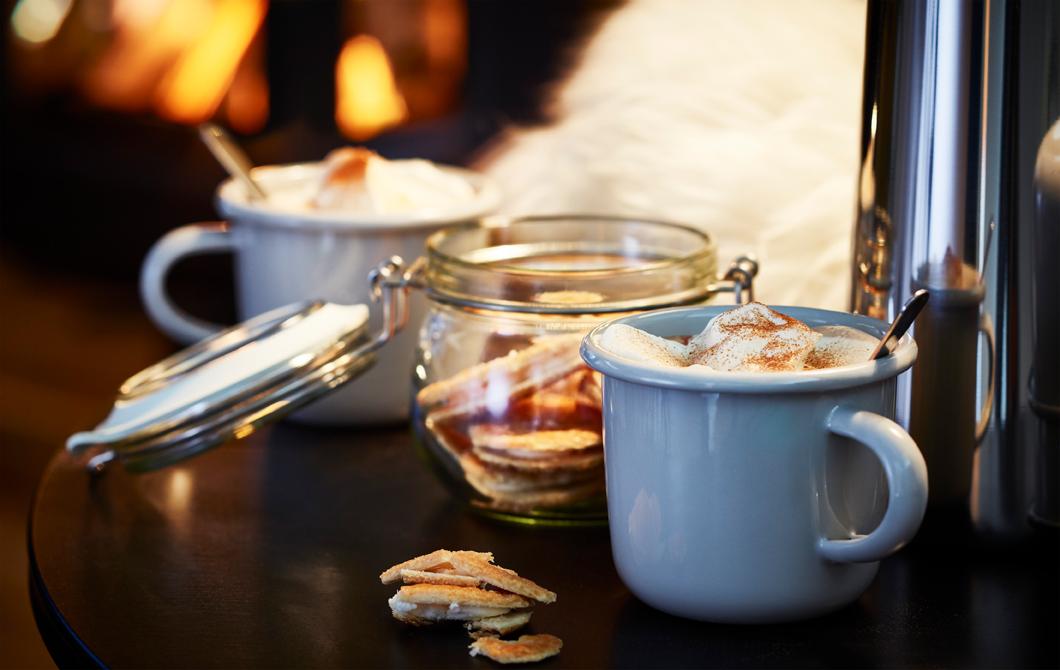 Маса с чаши с кафе и буркан с бисквити.