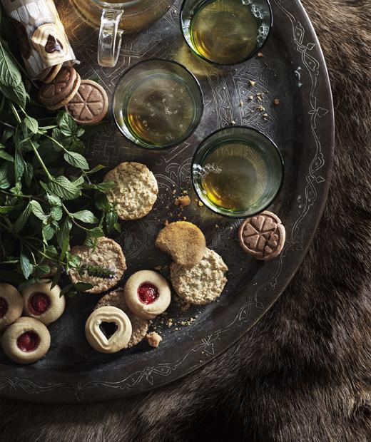 Разнообразни бисквити и чаши чай, подредени върху голям поднос.