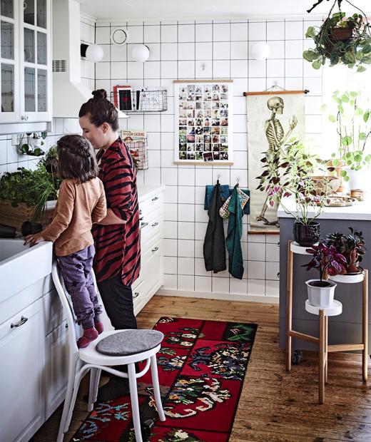 Кухня с бели шкафове, висящи кърпи и поставки за растения.