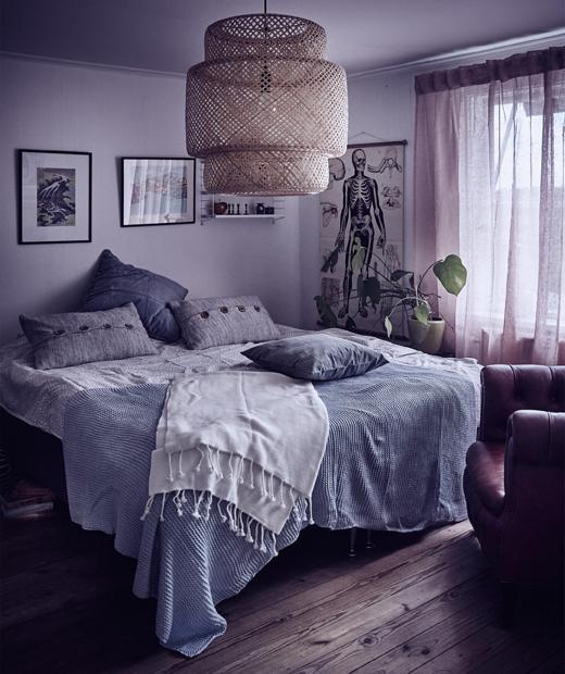 Уютна спалня със сиви стени и сиви и сини възглавници, хвърлени на легло, с дисяща над него лампа.