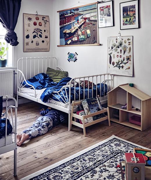 Забавна детска стая с бели стени, поставки за книги, къща за кукли и много картини по стените.