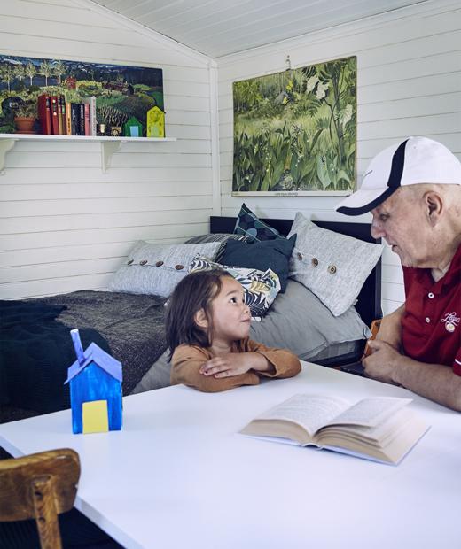 Дядо и внук седят на маса в стая с бели дървени стени.