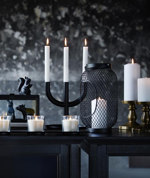 Различни бели сввещи и свещници на черна маса до черно-сива стена.