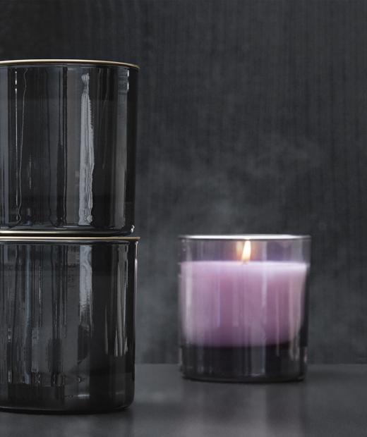 Приближен изглед към лилава свещ в стъклена поставка на сив фон.