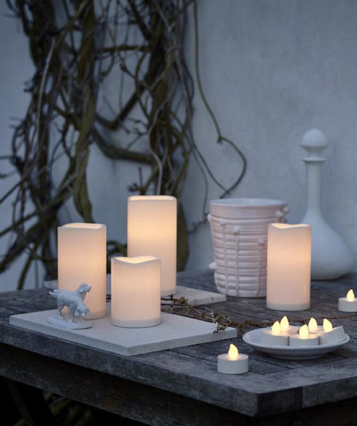 Различни LED свещи на дървена маса пред бяла стена.