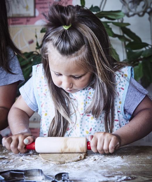 Дете точи тесто с точилка на маса с брашно.