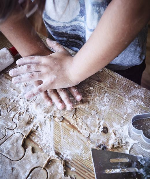 Приближен изглед на дете, което реже тесто с формички на покрита с брашно маса.