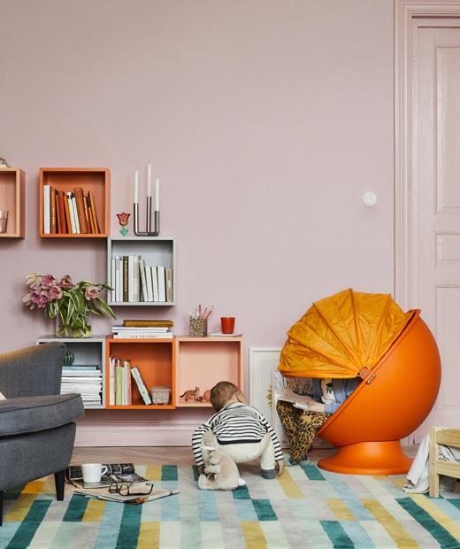 Цветна дневна с детски оранжев стол и две деца, които четат и играят.