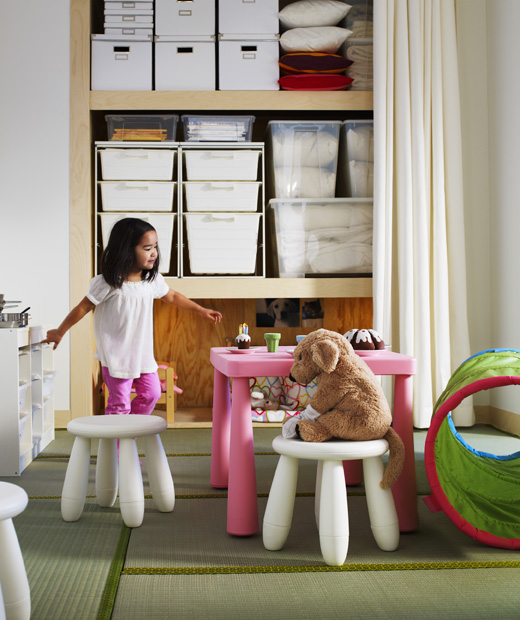 Дете организира чаено парти с плюшена играчка, на фона на отворени мебели за съхранение.