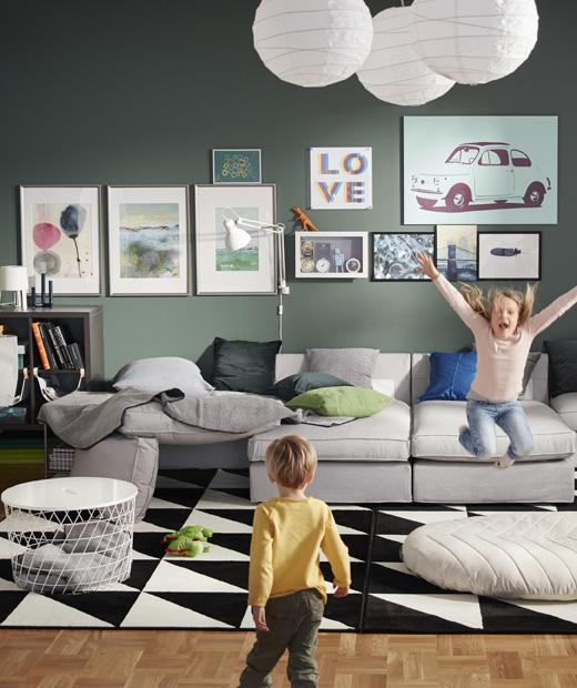 Зелена дневна с голям сив модулен диван и две играещи си деца.