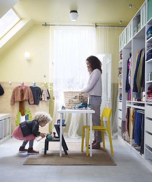 Ярка стая с отворени гардероби, жена подрежда пране на маса а дете си играе до нея.
