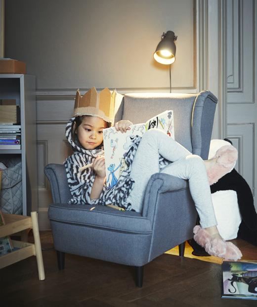 Момиче с картонена корона седи на сив стол и оцветява книжка.