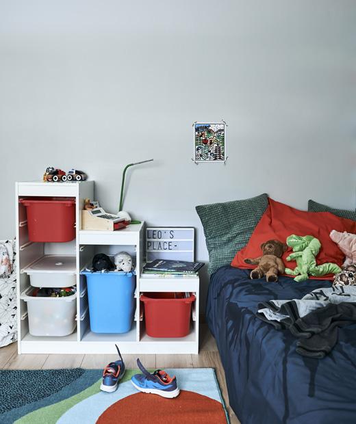 Детска стая с цветни мебели за съхранение, килим и легло с възглавници и играчки.