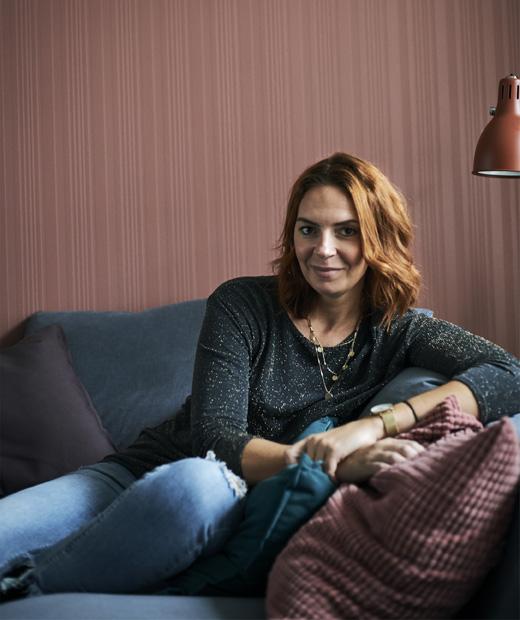 Снимка на Амели, седнала на сив диван на фона на червена стена.