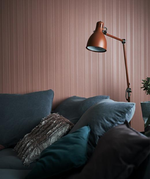 Червена лампа над сив диван пред червена стена.