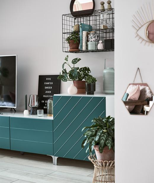 Цветя и украшения върху кабинет за телевизор със зелени врати.