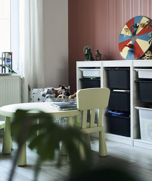Зелена детска маса и столове и мебели за съхранение с шкафчета.