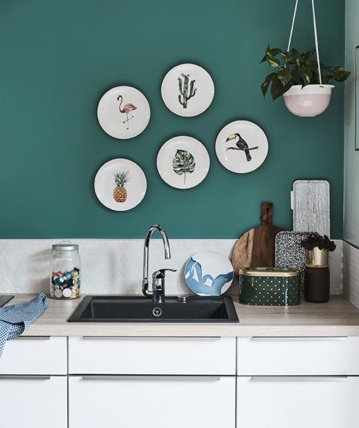 Бяла кухня с дървени плотове и зелена стена с декоративни чинии.