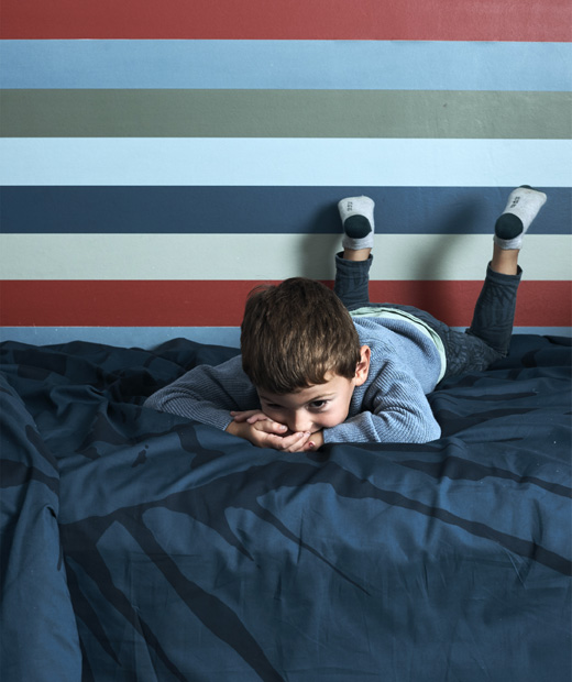 Момче лежи на легло с тъмносиня калъфка и шарен тапет.