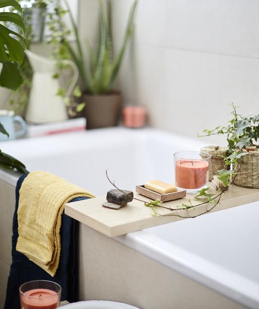 Свещи, сапун и растения на дървена поставка в баня.