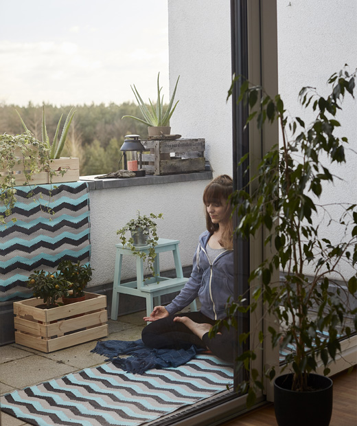 Ева практикува йога на постелка на балкон с растения.