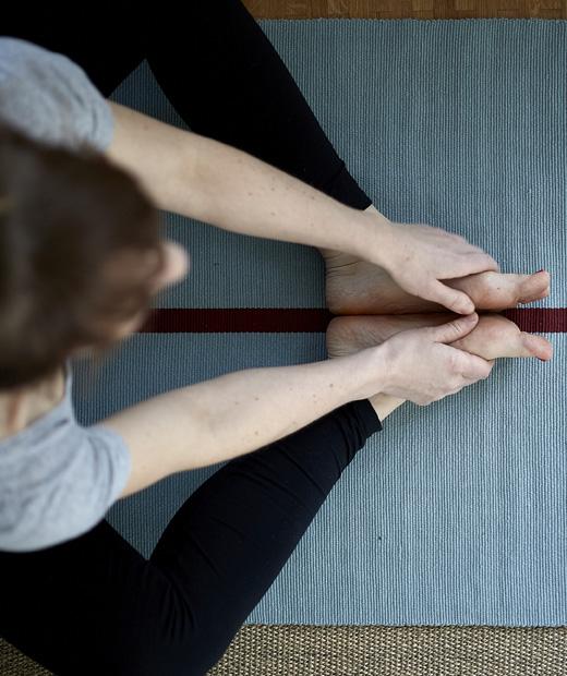 Поглед отгоре на Ева, практикуваща йога на синя постелка.