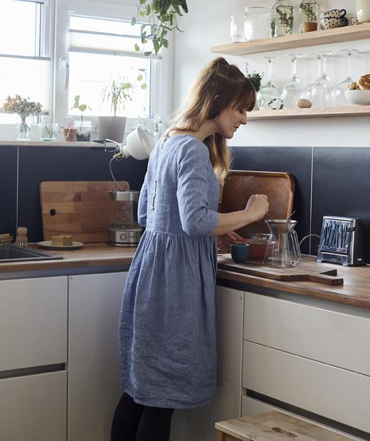 Жена приготвя чай в ъгъла на бяла и синя кухня.