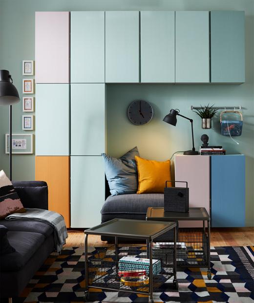Снимка на стая с шкафове на стена, часовник, настолна лампа и възглавници, диван и масички върху килим.