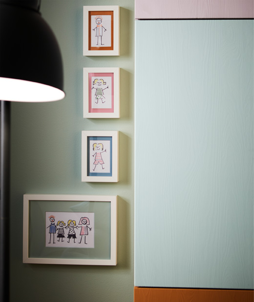Рамки на стена с детски рисунки в тях.
