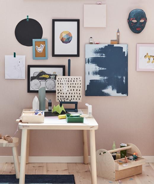 Картини и рисунки, поставени на розова стена над дървено бюро.