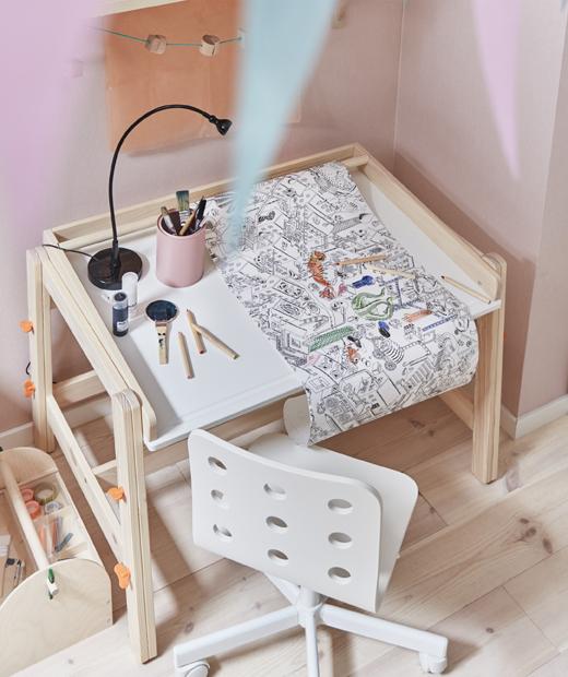 Ролка с хартия за оцветяване върху детско бюро с бял стол до розова стена.