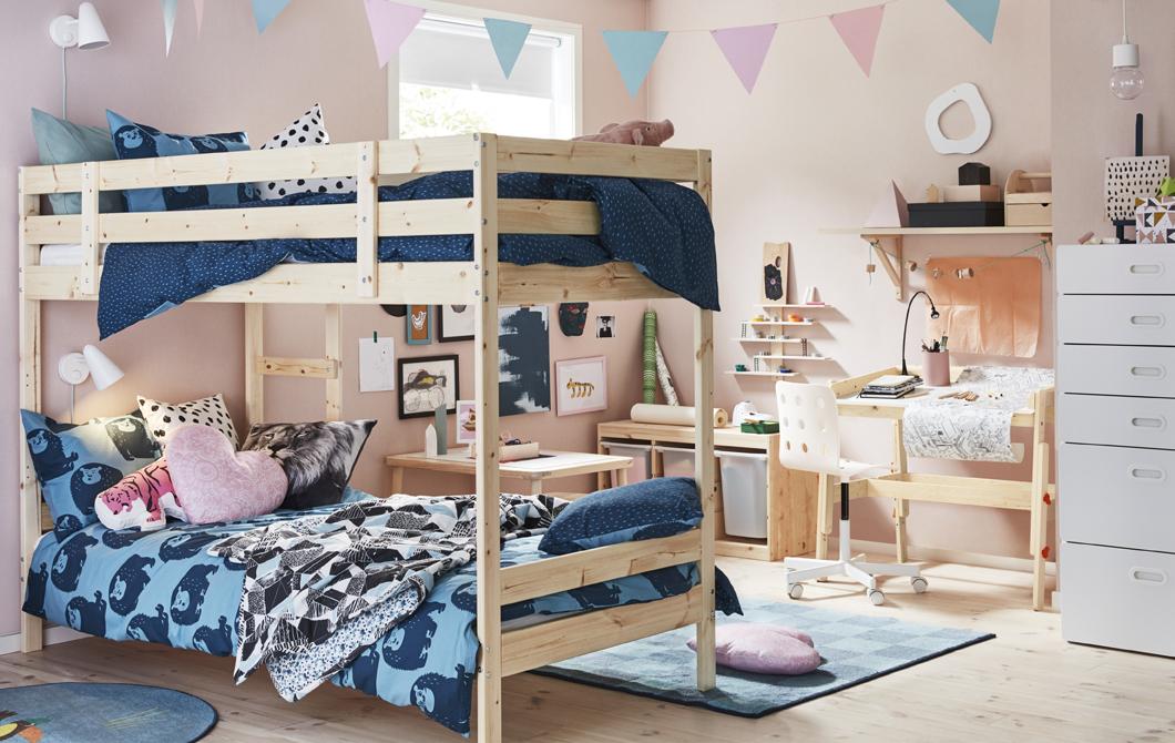 Детска стая с розови стени, легло на два етажа и дървено бюро.